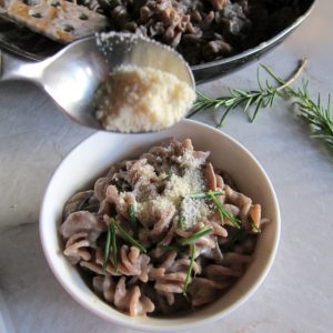 In a large pot, bring a quart of water to boil. Add 1 tablespoon salt to water and cook pasta according to package instructions. To make the sauce, heat a large nonstick pan over medium heat, add the butter and mushrooms, sauté, stirring occasionally, until the mushrooms are browned (8-10 minutes). Season with a pinch of salt and pepper, add the garlic and continue to cook for 3-5 minutes until the garlic is fragrant. Sprinkle the flouer over the mushrooms and cook for 3 minutes, stirring to evenly coat the mushrooms. Add the chicken broth to the pan and stir. Let the sauce bubble over medium high heat for 10-15 minutes until it has slightly thickened. In the meantime, finish cooking the pasta and drain it. Taste the sauce, add salt and pepper to taste. Remove the sauce from the heat, stir in the yogurt and rosemary. Add the pasta to the sauce in the skillet, toss to coat the pasta,serve with Parmesan cheese if desired.